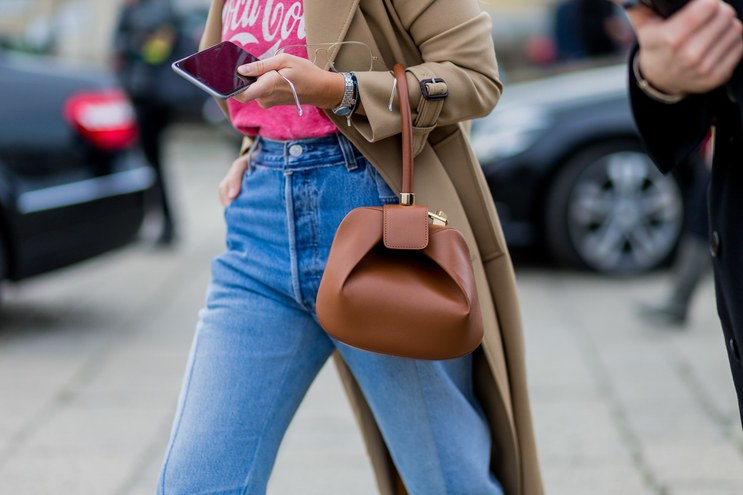 MILAN, ITALY - FEBRUARY 24:  Miroslava Duma wearing a trench coat a Coca Cola shirt, blue denim jeans and a Loewe bag seen outside Gucci during Milan Fashion Week Fall/Winter 2016/17 on February 24, 2016 in Milan, Italy (Photo by Christian Vierig/Getty Images)
