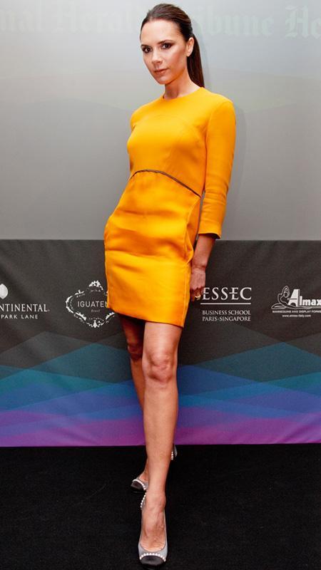 Victoria Beckham in orange dress