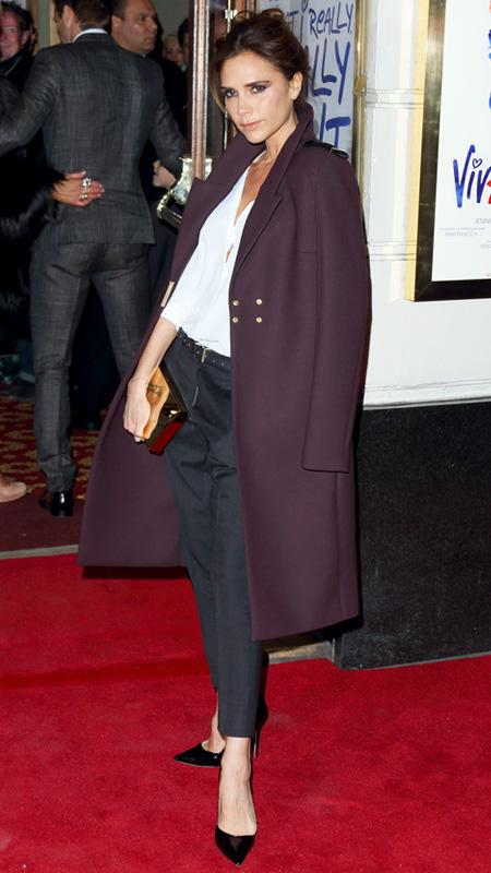Victoria Beckham with navy pants, white button down, and plum coat
