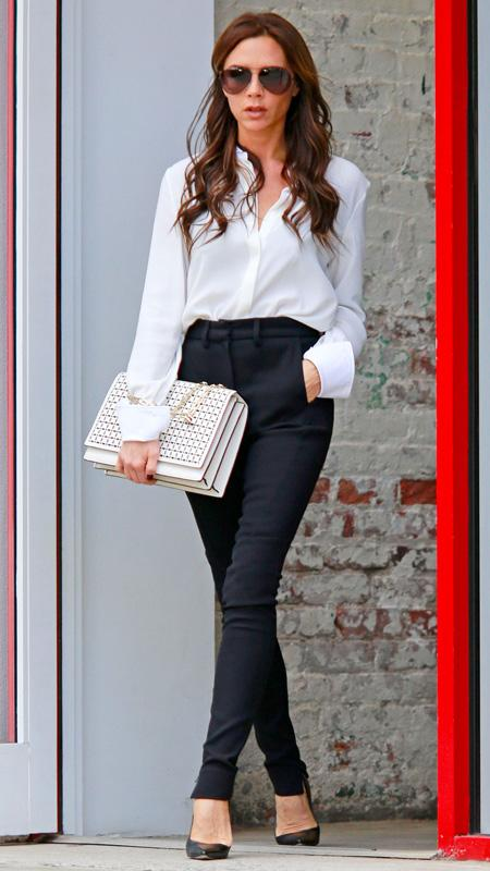 Victoria Beckham with white button-down and black pants white oversized clutch
