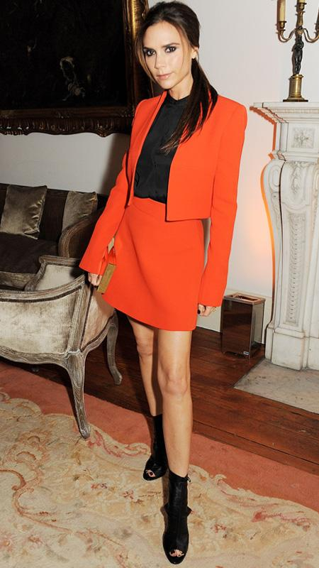 Victoria Beckham in red blazer and mini skirt with black open toe boots